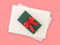 Green gift box with red ribbon bow and white envelope with light purple greeting card on pink background Stock Photo