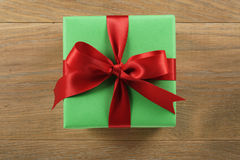 Green gift box with red ribbon bow on wooden oak table from above Stock Image