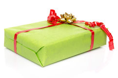 Green gift box with a red ribbon and a golden bow Royalty Free Stock Photos