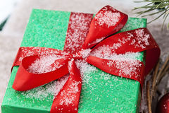 Green gift box with a red ribbon sprinkled with snow close-up Stock Photos