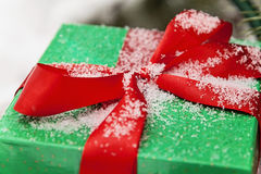 Green gift box with a red ribbon sprinkled with snow close-up Stock Photography
