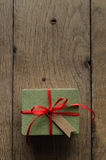 Green Gift Box with Red Ribbon and Vintage Style Blank Tag. Overhead shot of a simple green gift box on an old oak wood planked table, tied to a bow with red Stock Images