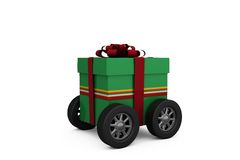 Green gift box with red ribbon on wheels Royalty Free Stock Image