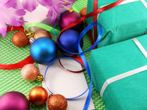Green gift box with a white ribbon and new year balls Stock Images