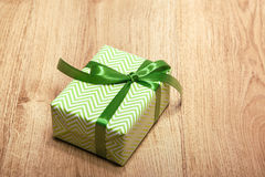 Green gift box on wood desk. Green gift box and shiny ribbon on wood desk Stock Photography