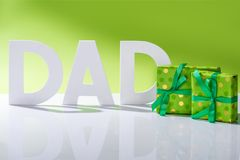 Green gift boxes in front of dad inscription made of white letters on green, Happy fathers. Day concept royalty free stock images