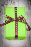 Green gift for Christmas or other celebration on wooden plank Royalty Free Stock Photography