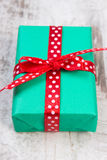 Green gift for Christmas or other celebration on wooden plank Stock Photography