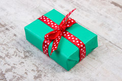 Green gift for Christmas or other celebration on wooden plank Stock Images