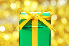 Green gift on red blurry lights background. Royalty Free Stock Photos