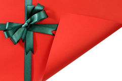 Green gift ribbon bow on plain red background paper, corner folded open showing white copy space inside Stock Images