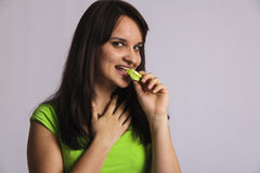 GREEN. Girl in green shirt eat lime macaron Royalty Free Stock Photos