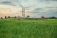 A green glade on background of the industrial zone Stock Images