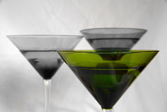 Green Glass. A green martini glass against two muted glasses in the background Stock Image