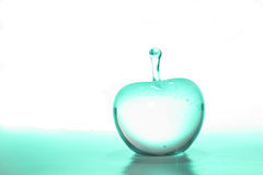 Green Glass Apple. A glass apple with green light within and in the foreground, against a white background Stock Image