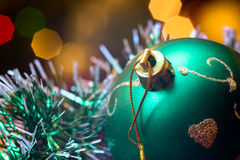 Green glass ball lie in Christmas tinsel. Royalty Free Stock Photos