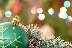 Green glass ball lie in Christmas tinsel. Royalty Free Stock Images