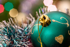 Green glass ball lie in Christmas tinsel. Stock Photo