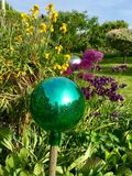 Green glass ball. On stick in the garden royalty free stock images