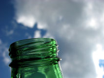 Green glass and blue sky. Green glass bottle raised to a blue sky with white clouds Royalty Free Stock Photo