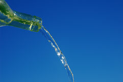Green Glass Bottle. Water Pouring From A Green Glass Bottle Royalty Free Stock Photography