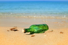 Green glass bottle with a letter at beach Stock Photography