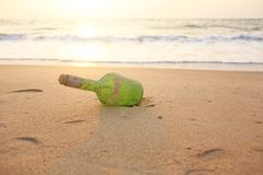 Green glass bottle with a message inside on the seashore on the beach. Magic and fairy tale. Design with copy space royalty free stock photography