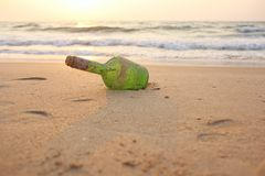 Green glass bottle with a message inside on the seashore on the royalty free stock images