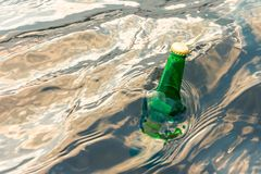 Green glass bottle in the sea with a message. Green glass bottle in the sea with a message stock image