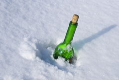 Green glass bottle in the snow Royalty Free Stock Photo