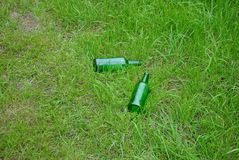 Green glass bottles. On the lawn Stock Photos