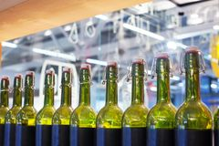 Green glass bottles of wine in row on wood shelf, bar interior design, preparation of alcoholic cocktails, wine tasting concept stock photography