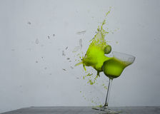 Green glass breaking. Breaking a glass with a green liquid inside Royalty Free Stock Photo