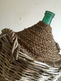 Green glass demijohn. Close up of a green glass demijohn in wicker basket used to ferment wine Stock Photos