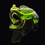 Green glass frog on black. Glass figurine of a green frog green on a black background with shadow isolated Royalty Free Stock Photo