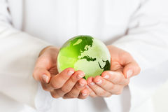 Green glass globe in hand Stock Photos