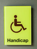 Green glass handicap sign on grey wall Stock Photography