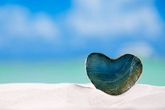 Green glass heart on white sand beach, Royalty Free Stock Images