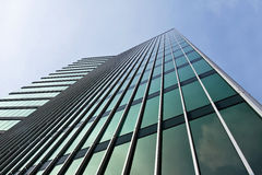 Green Glass Office Tower. Angular office tower with green windows against blue sky Stock Photos