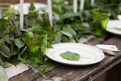 Green glass, white plate with green leave. Silver spoon and fork with blank label on wooden table and candles, green leaves, eucalyptus on background outdoors Royalty Free Stock Photo
