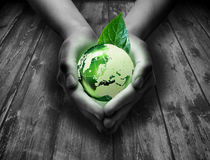 Green glass world in the heart hand. Wood background stock images