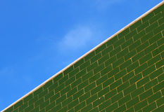 Green glazed tile wall and the blue sky Stock Image