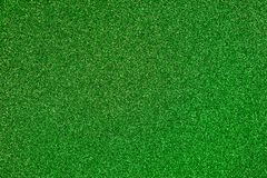 Green Glitter Background. Lime green colored sand paper textured background with sparkles and glitters stock image