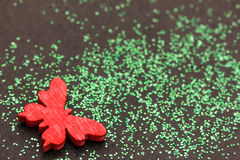 Green glitter and a red butterfly Royalty Free Stock Photos