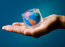 Green - Global warming. Conceptual image of global warming and green environmentalism. Human hand holding earth globe frozen into thawing ice cube Royalty Free Stock Image