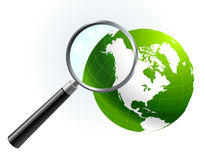 Green Globe under magnifying glass Stock Image