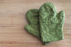 Green glove on a wooden table.