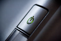 Green glowing power button. Closeup shot Royalty Free Stock Photography