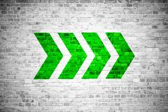 Green go ahead directional arrow signs pointing direction painted on a white gray brick wall stock images