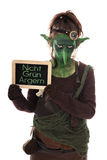 Green goblin holding a slate with german text, not to be extreme Royalty Free Stock Photo